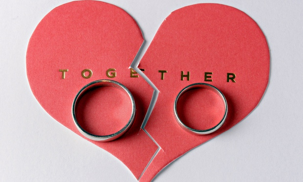 A pair of wedding rings pictured on a broken cardboard heart