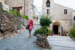 Girl walking through the typical narrow streets of Castelmola, a small tourist village near Taormina, Sicily